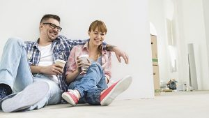 Couple sitting on the floor of a house they've just bought